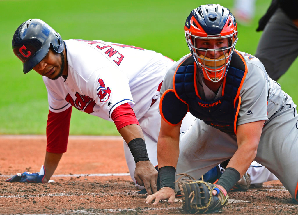 . Cleveland Indians\' Edwin Encarnacion, left, touches home plate as Detroit Tigers catcher James McCann looks for the ball the first inning of a baseball game, Saturday, June 23, 2018, in Cleveland. Encarnacion scored on a single by Brandon Guyer and error by McCann. (AP Photo/David Dermer)