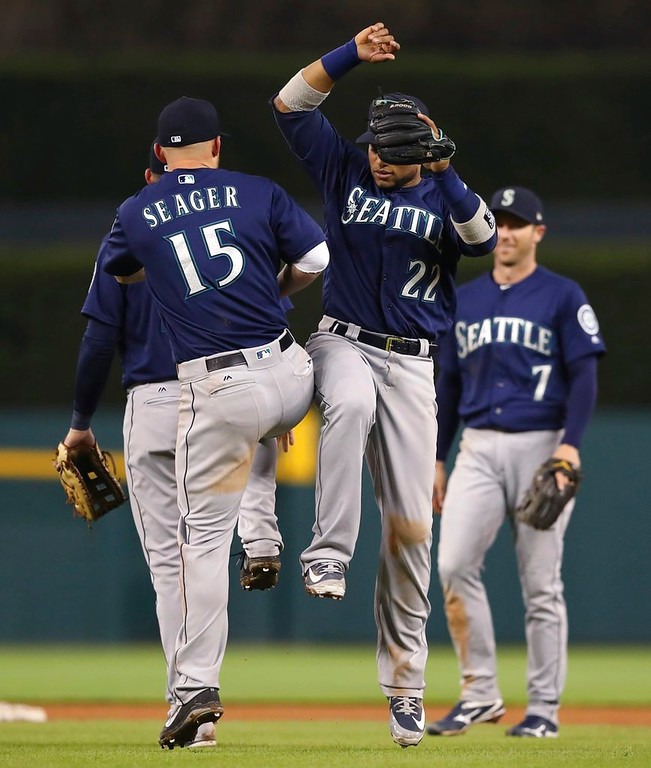 . Seattle Mariners third baseman Kyle Seager (15) and second baseman Robinson Cano (22) celebrate the team\'s 9-5 win over the Detroit Tigers in the second game of a baseball doubleheader, Saturday, May 12, 2018, in Detroit. (AP Photo/Carlos Osorio)