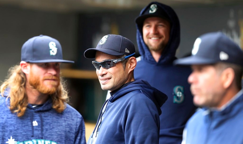 . Seattle Mariners bench coach Ichiro Suzuki, center, stands with teammates before the first inning of game one of a baseball doubleheader against the Detroit Tigers, Saturday, May 12, 2018, in Detroit. (AP Photo/Carlos Osorio)