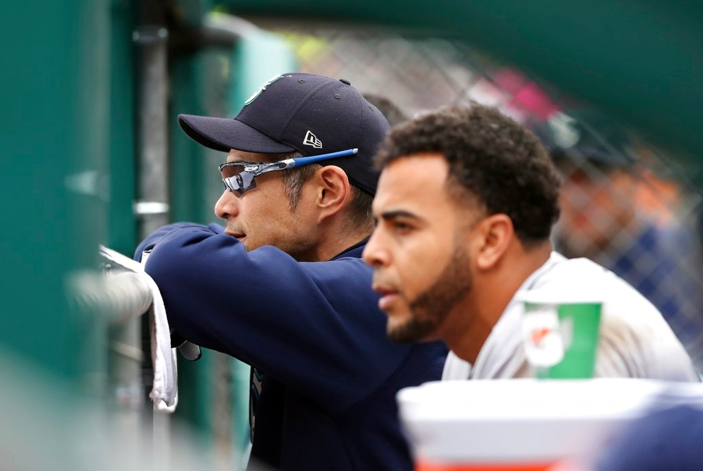 . Seattle Mariners bench coach Ichiro Suzuki, left, stands with designated hitter Nelson Cruz in the dugout during the fourth inning of game one of a baseball doubleheader against the Detroit Tigers, Saturday, May 12, 2018, in Detroit. (AP Photo/Carlos Osorio)