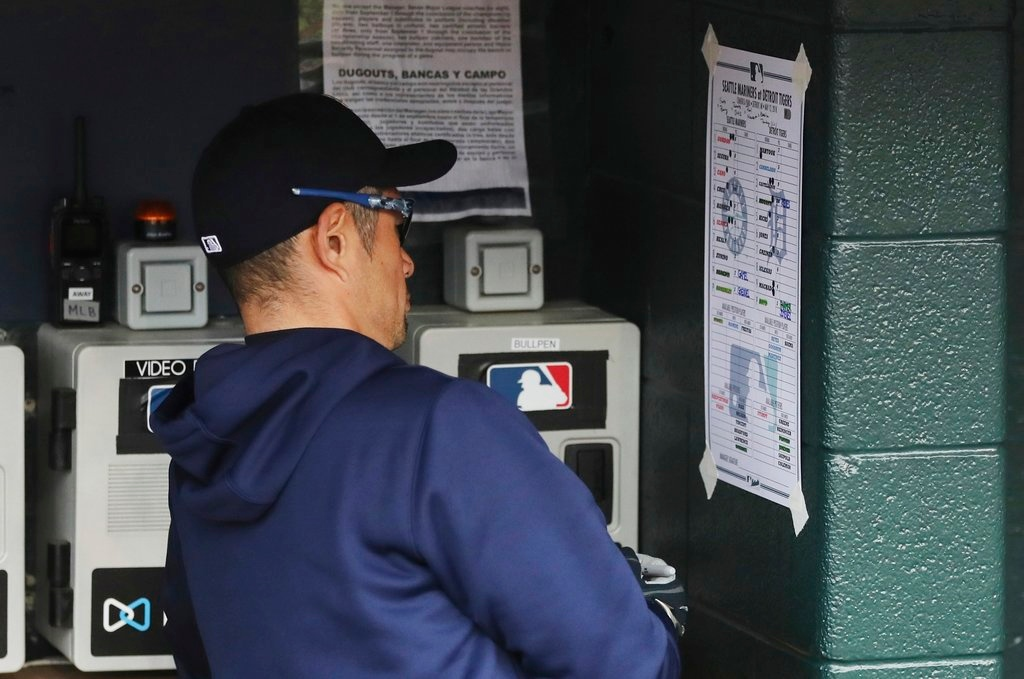 . Seattle Mariners acting bench coach Ichiro Suzuki looks over the lineup during the ninth inning of game one of a baseball doubleheader against the Detroit Tigers, Saturday, May 12, 2018, in Detroit. (AP Photo/Carlos Osorio)