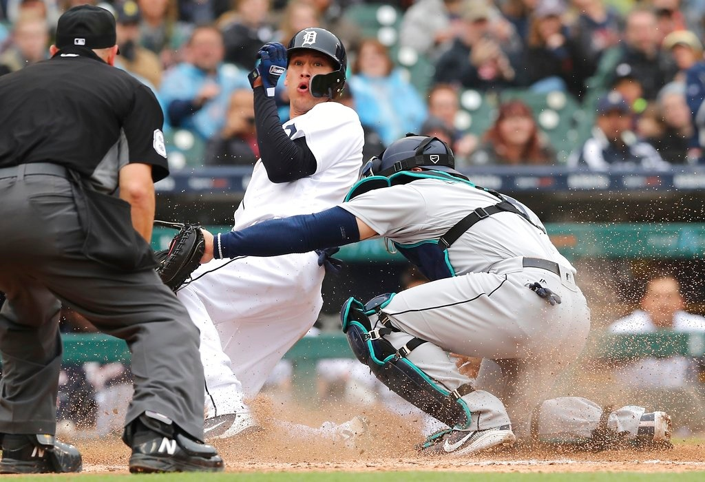 . Detroit Tigers\' JaCoby Jones, center, reacts near umpire Scott Barry, left, as he safely beats the throw to Seattle Mariners catcher Mike Zunino, right, and scores during the sixth inning of game one of a baseball doubleheader, Saturday, May 12, 2018, in Detroit. (AP Photo/Carlos Osorio)