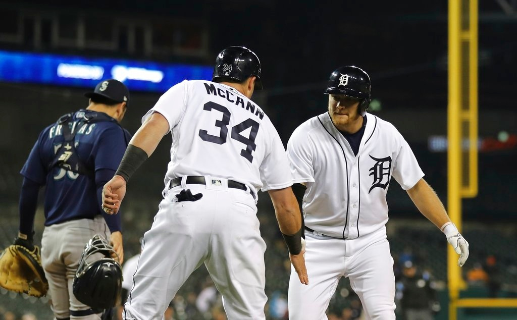 . Detroit Tigers\' James McCann (34) congratulates John Hicks after they both scored on Hicks\' two-run home run during the fifth inning of the second game of a baseball doubleheader against the Seattle Mariners, Saturday, May 12, 2018, in Detroit. (AP Photo/Carlos Osorio)