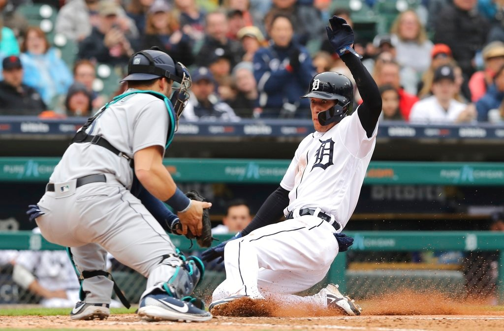 . Detroit Tigers\' JaCoby Jones safely beats the throw to Seattle Mariners catcher Mike Zunino and scores during the sixth inning of game one of a baseball doubleheader, Saturday, May 12, 2018, in Detroit. (AP Photo/Carlos Osorio)