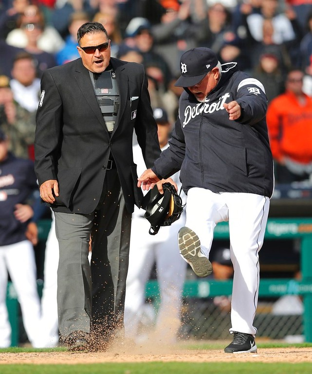 . Detroit Tigers manager Ron Gardenhire, right, kicks dirt onto home plate next to umpire Tony Randazzo after a play was overturned during the tenth inning of a baseball game against the Pittsburgh Pirates, Friday, March 30, 2018, in Detroit. Gardenhire was ejected by Randazzo. (AP Photo/Carlos Osorio)