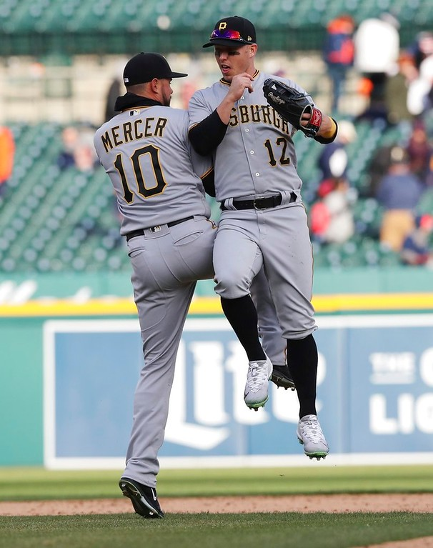 . Pittsburgh Pirates shortstop Jordy Mercer (10) and left fielder Corey Dickerson (12) celebrate after a win over the Detroit Tigers in the 13th inning of a baseball game, Friday, March 30, 2018, in Detroit. (AP Photo/Carlos Osorio)