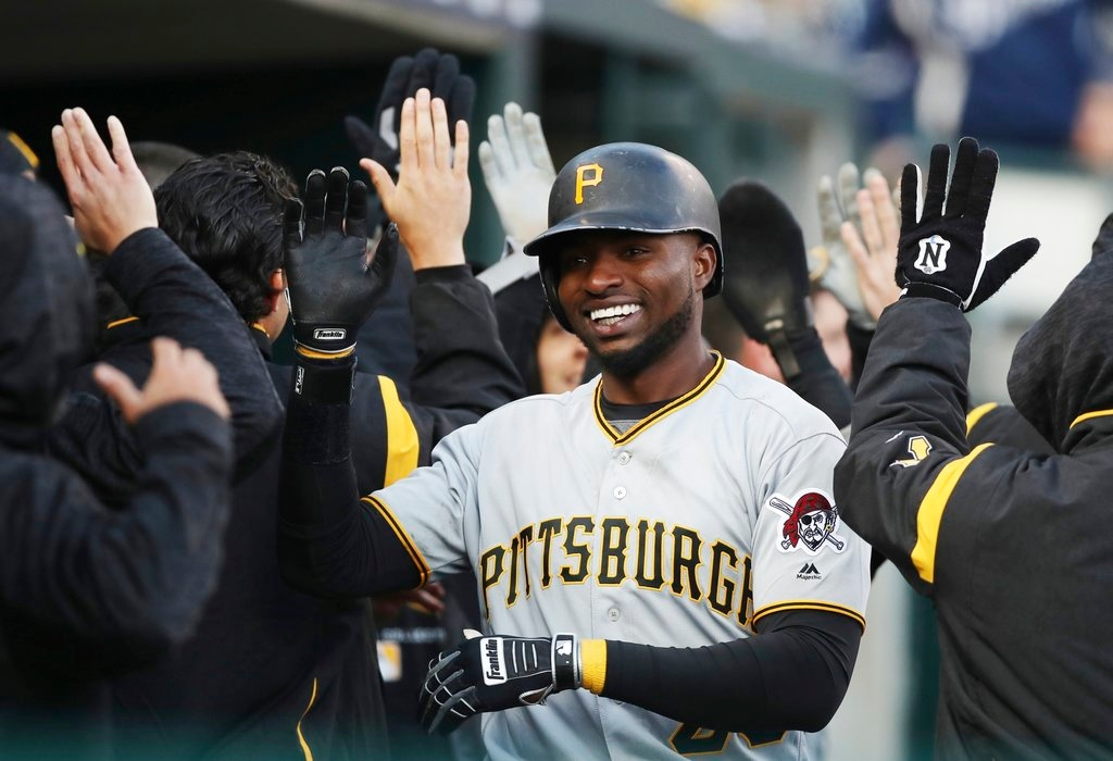 . Pittsburgh Pirates\' Gregory Polanco is congratulated in the dugout after his three-run home run during the 13th inning of a baseball game against the Detroit Tigers, Friday, March 30, 2018, in Detroit. (AP Photo/Carlos Osorio)
