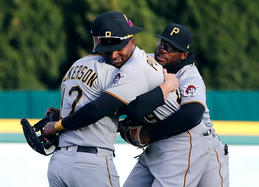 . From left to right, Pittsburgh Pirates outfielders Corey Dickerson, Gregory Polanco and Starling Marte hug after they defeated the Detroit Tigers in the 13th inning of a baseball game, Friday, March 30, 2018, in Detroit. (AP Photo/Carlos Osorio)