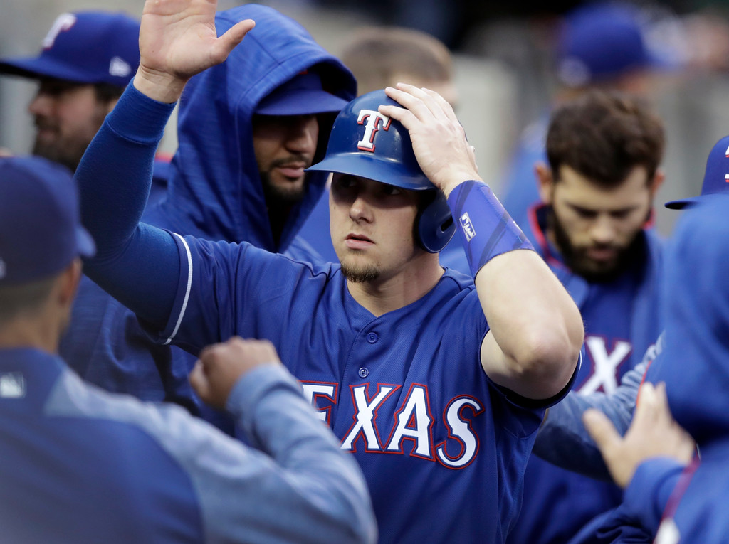 . Texas Rangers\' Ryan Rua is congratulated in the dugout after scoring from third on a bases-loaded walk to Elvis Andrus during the third inning of a baseball game against the Detroit Tigers, Friday, May 19, 2017, in Detroit. (AP Photo/Carlos Osorio)