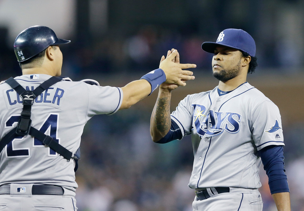 . Tampa Bay Rays relief pitcher Alex Colome, right, and catcher Hank Conger shake hands after the Rays defeated the Detroit Tigers 7-5 in a baseball game, Friday, May 20, 2016, in Detroit. (AP Photo/Carlos Osorio)