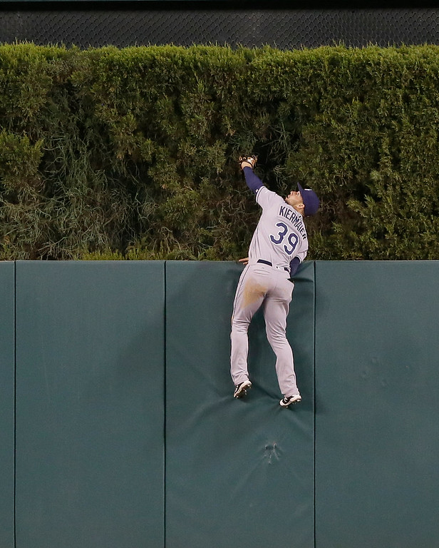 . Tampa Bay Rays center fielder Kevin Kiermaier jumps on the outfield fence in attempt to reach the solo home run by Detroit Tigers\' Miguel Cabrera during the seventh inning of a baseball game, Friday, May 20, 2016, in Detroit. (AP Photo/Carlos Osorio)