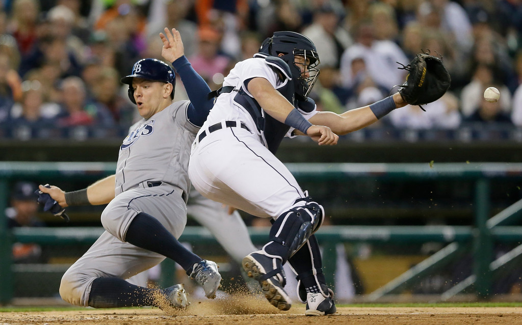. Detroit Tigers catcher James McCann waits on the throw as Tampa Bay Rays\' Logan Morrison slides during the sixth inning of a baseball game, Friday, May 20, 2016, in Detroit. (AP Photo/Carlos Osorio)