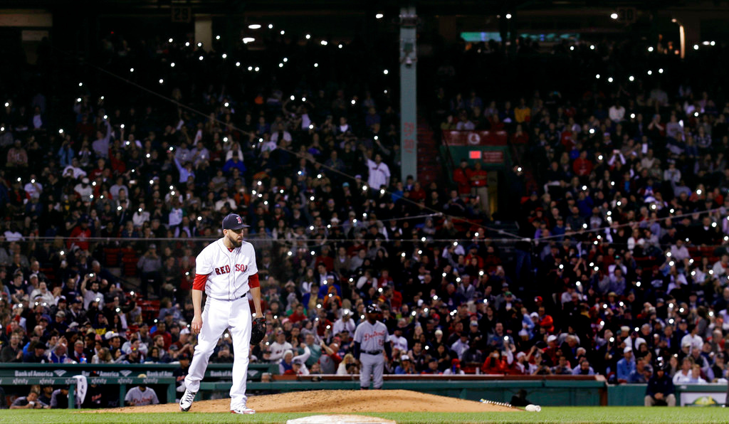. Fans turn on the flashlight on their cellphones as Boston Red Sox relief pitcher Matt Barnes walks back to the mound during the seventh inning of the team\'s baseball game against the Detroit Tigers at Fenway Park in Boston, Wednesday, June 6, 2018. (AP Photo/Charles Krupa)
