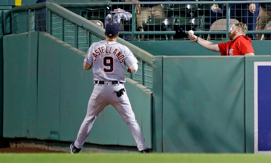 . Detroit Tigers center fielder Nicholas Castellanos (9) watches as Boston Red Sox\'s bullpen catcher Mike Brenly, right, tries to catch a solo home run by Andrew Benintendi with his cap during the fourth inning of a baseball game at Fenway Park in Boston, Wednesday, June 6, 2018. (AP Photo/Charles Krupa)