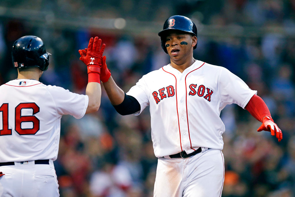 . Boston Red Sox\'s Rafael Devers, right, is congratulated by Andrew Benintendi (16) after scoring on a double by Christian Vazquez during the third inning of a baseball game against the Detroit Tigers at Fenway Park in Boston, Wednesday, June 6, 2018. (AP Photo/Charles Krupa)