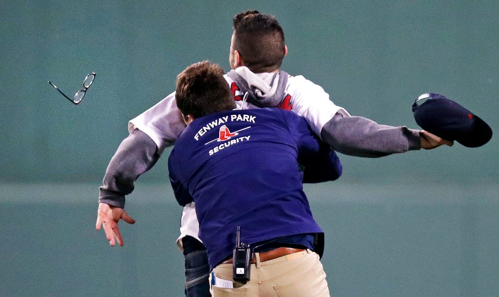 . A Fenway Park security worker loses his eyeglasses as he tackles a fan who ran onto the field during the fifth inning of a baseball game against the Detroit Tigers in Boston, Wednesday, June 6, 2018. (AP Photo/Charles Krupa)