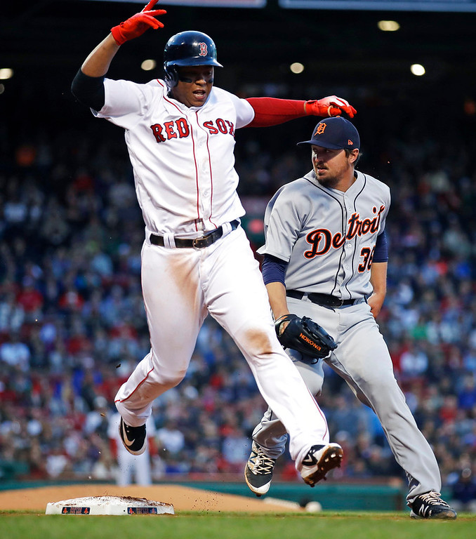 . Boston Red Sox\'s Rafael Devers, left, legs out a single as the ball gets away from Detroit Tigers relief pitcher Blaine Hardy, right, who was covering first base, during the third inning of a baseball game at Fenway Park in Boston, Wednesday, June 6, 2018. (AP Photo/Charles Krupa)