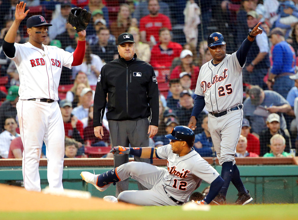 . Detroit Tigers\' Leonys Martin (12) slides in for a triple as Boston Red Sox third baseman Rafael Devers, left, gestures to hold the throw in the third inning of a baseball game at Fenway Park, Thursday, June 7, 2018, in Boston. At right is Tigers third base coach Dave Clark (25). (AP Photo/Elise Amendola)