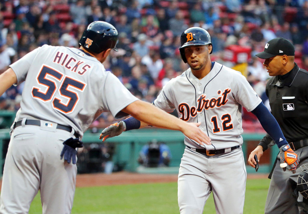 . Detroit Tigers\' Leonys Martin (12) is greeted at the plate by John Hicks (55) after his two-run home run during the first inning of a baseball game against the Boston Red Sox at Fenway Park, Thursday, June 7, 2018, in Boston. (AP Photo/Elise Amendola)