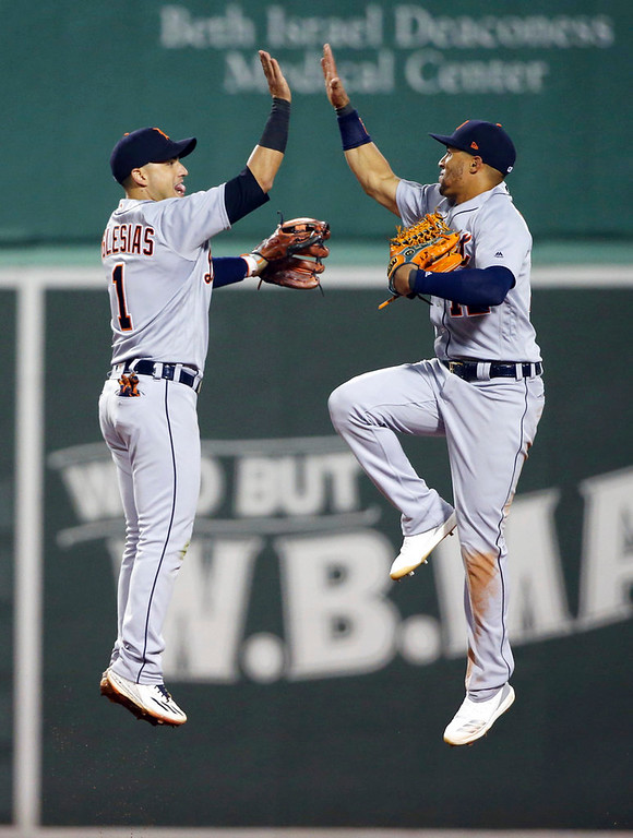 . Detroit Tigers shortstop Jose Iglesias, left, and center fielder Leonys Martin celebrate the Tigers\' 7-2 victory over the Boston Red Sox in a baseball game at Fenway Park, Thursday, June 7, 2018, in Boston. (AP Photo/Elise Amendola)