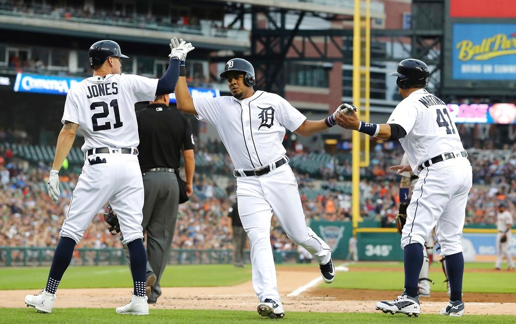. Detroit Tigers\' Jeimer Candelario, center, and designated hitter Victor Martinez (41) are greeted by JaCoby Jones (21) after scoring on a two-run double by Jose Iglesias during the second inning of a baseball game against the Boston Red Sox, Saturday, July 21, 2018, in Detroit. (AP Photo/Carlos Osorio)