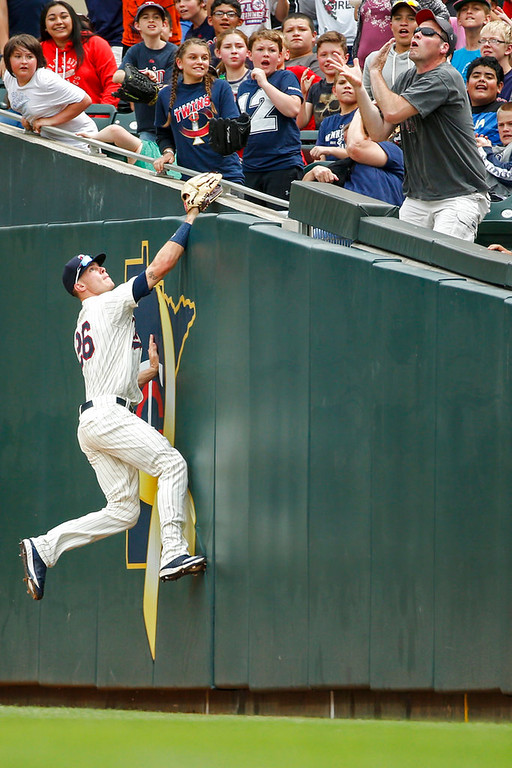 . Minnesota Twins right fielder Max Kepler leaps for a foul ball that a fan catches from the bat of the Detroit Tigers in the ninth inning of a baseball game Wednesday, May 23, 2018, in Minneapolis. The Tigers won 4-1.(AP Photo/Bruce Kluckhohn)