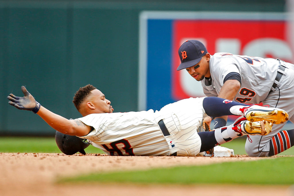 . Minnesota Twins Byron Buxton avoids the tag of Detroit Tigers shortstop Dixon Machado to get a double in the fifth inning of a baseball game Wednesday, May 23, 2018, in Minneapolis. The Tigers won 4-1.(AP Photo/Bruce Kluckhohn)