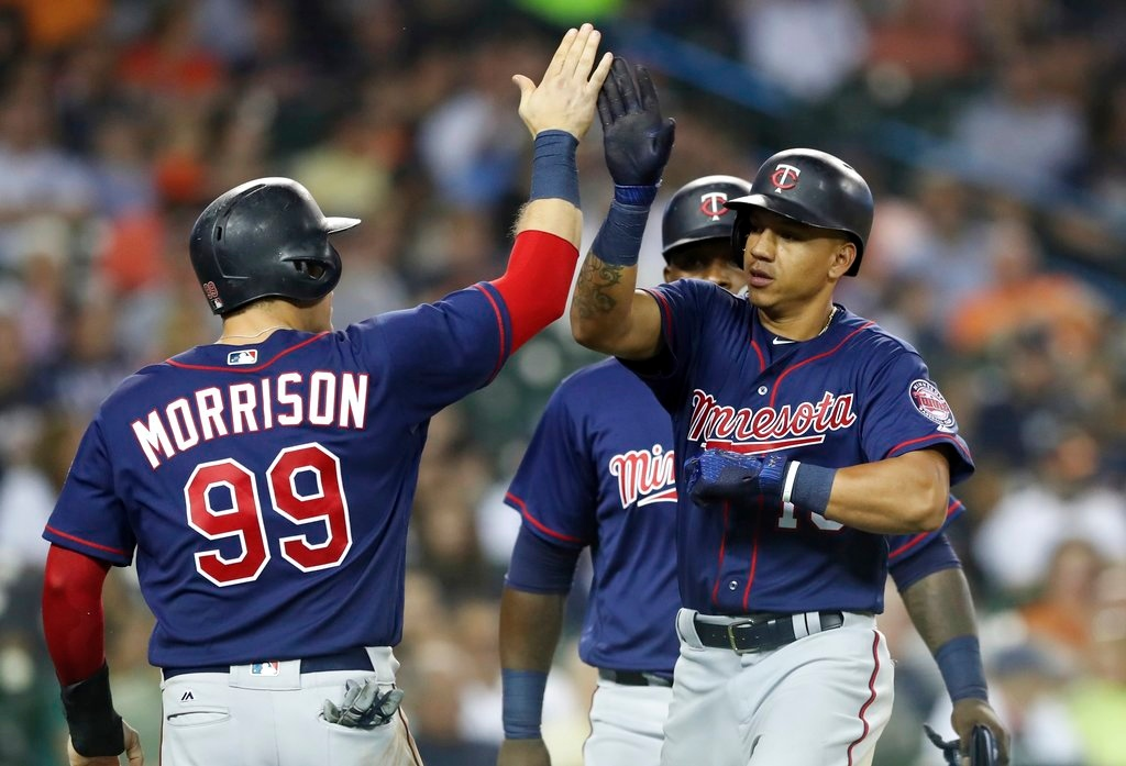 . Minnesota Twins\' Ehire Adrianza, right, is greeted by Logan Morrison (99) and Miguel Sano, rear, after they scored on Adrianza\'s grand slam during the seventh inning of a baseball game against the Detroit Tigers, Tuesday, June 12, 2018, in Detroit. (AP Photo/Carlos Osorio)