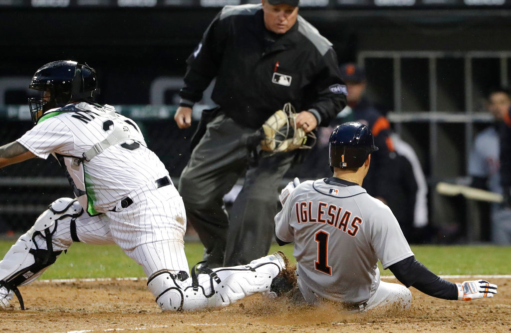 . Detroit Tigers\' Jose Iglesias, right, scores on a single by Jaime Candelario as Chicago White Sox catcher Omar Narvaez waits for the ball during the 10th inning of a baseball game Thursday, April 5, 2018, in Chicago. The Tigers won 9-7. (AP Photo/Nam Y. Huh)