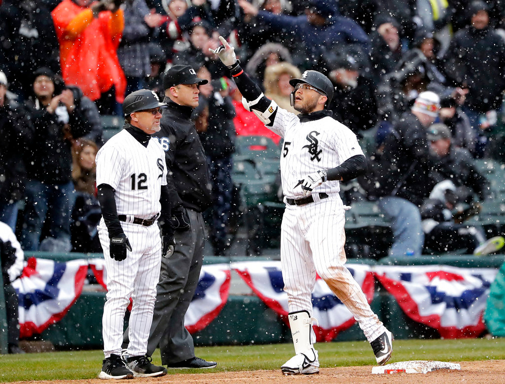 . Chicago White Sox\'s Yolmer Sanchez, right, celebrates after hitting a one-run triple as third base coach Nick Capra looks to the field during the fifth inning of the White Sox season home-opener baseball game against the Detroit Tigers, Thursday, April 5, 2018, in Chicago. (AP Photo/Nam Y. Huh)