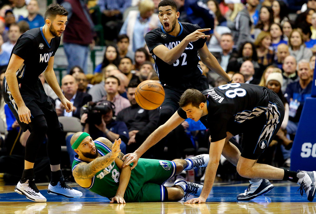 . Dallas Mavericks guard Deron Williams (8) tries to pass from the floor against Minnesota Timberwolves defenders Nemanja Bjelica (88), Karl-Anthony Towns (32) and Ricky Rubio (9) during the first half of an NBA basketball game Wednesday, Jan. 20, 2016, in Dallas. (AP Photo/LM Otero)