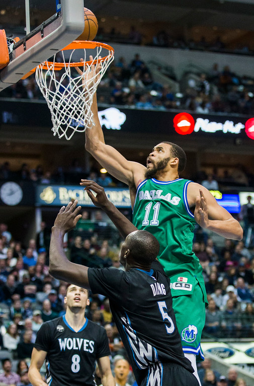 . The Dallas Mavericks\' JaVale McGee (11) takes a shot over the Minnesota Timberwolves\' Zach LaVine (8) and Gorgui Dieng (5) during the second quarter on Wednesday, Jan. 20, 2016, at the American Airlines Center in Dallas. (Ashley Landis/Dallas Morning News/TNS)