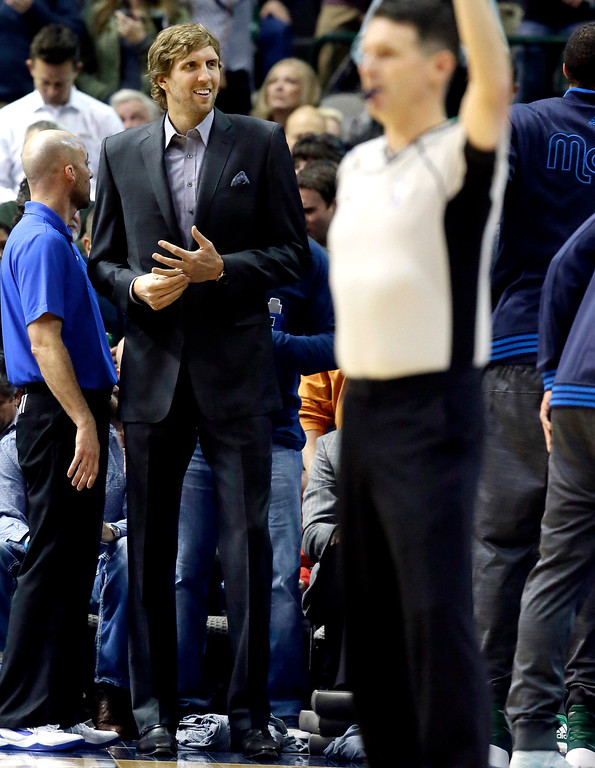 . Dallas Mavericks forward Dirk Nowitzki (41) wears a suit on the sidelines during the first half of an NBA basketball game against the Minnesota Timberwolves Wednesday, Jan. 20, 2016, in Dallas. Nowitzki was given the night off to rest. (AP Photo/LM Otero)