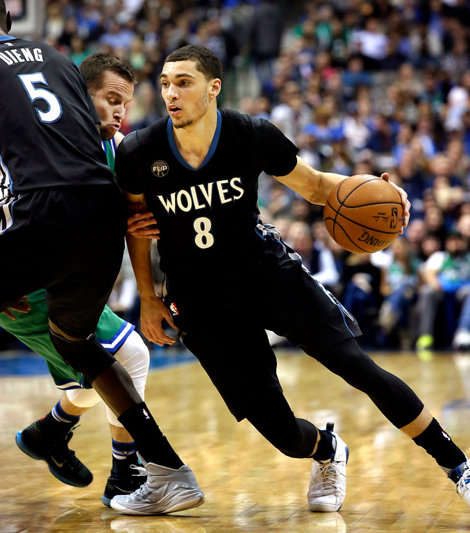. Minnesota Timberwolves guard Zach LaVine (8) uses a screen by teammate Gorgui Dieng (5) to stop Dallas Mavericks guard J.J. Barea (5) during the first half of an NBA basketball game Wednesday, Jan. 20, 2016, in Dallas. (AP Photo/LM Otero)