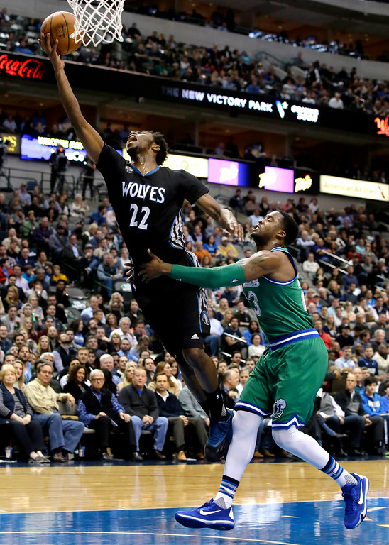 . Minnesota Timberwolves guard Andrew Wiggins (22) is fouled by Dallas Mavericks guard Wesley Matthews (23) during the first half of an NBA basketball game Wednesday, Jan. 20, 2016, in Dallas. (AP Photo/LM Otero)