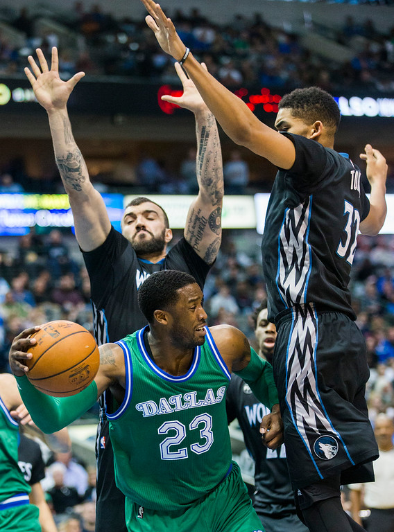 . The Dallas Mavericks\' Wesley Matthews (23) passes under the Minnesota Timberwolves\' Nikola Pekovic (14) and Karl-Anthony Towns (32) during the second quarter on Wednesday, Jan. 20, 2016, at the American Airlines Center in Dallas. (Ashley Landis/Dallas Morning News/TNS)