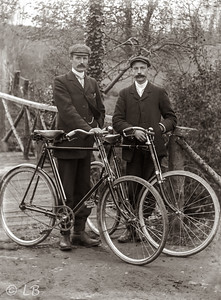 Two men with bicycles by bridge