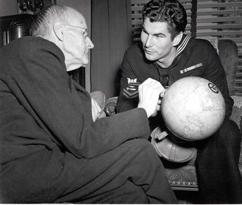 Paul Harris and unidentified sailor looking at a globe at Comely Bank, Harris's home in Chicago, Illinois, USA. December 1942.