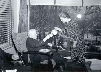 Jean Harris serves tea to Barney Arntzen at a reunion of the earliest members of the Rotary Club of Chicago at Comely Bank. December 1942.