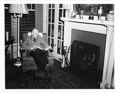 Paul Harris reads by the fire at Comely Bank in Chicago, Illinois, USA. December 1942.