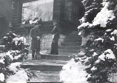 Paul Harris speaks with an unidentified man on the steps in front of Comely Bank in Chicago. December 1942.