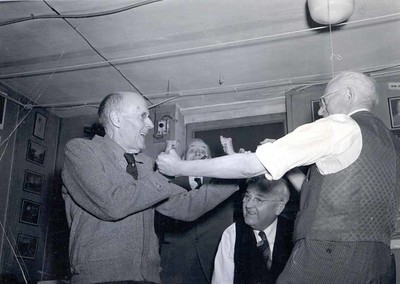 "Paul Harris and Montague ""Monty"" Bear having a ""boxing match"" as Barney Arntzen and Harry Ruggles look on at a reunion of the earliest members of the Rotary Club of Chicago at Comely Bank. December 1942."