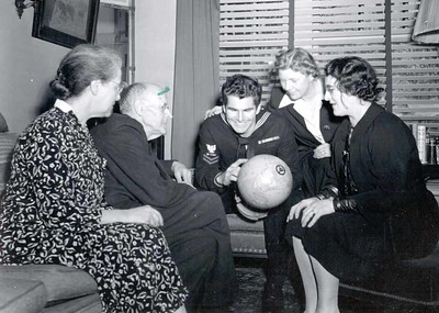 Jean and Paul Harris, an unidentified sailor, and two unidentified women look at a globe at Comely Bank. December 1942.
