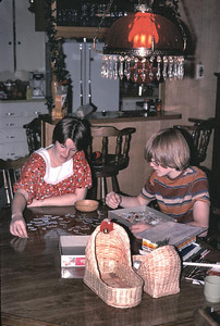 Kathy is awaiting the arrival of Erika so she and John are working on a puzzle.