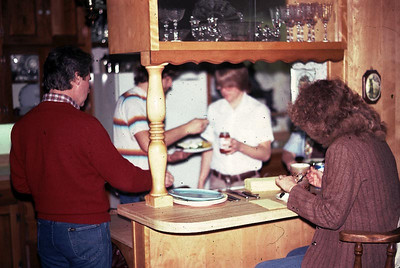 Cake is being served to Mike, Linda and Gary and John in the kitchen.