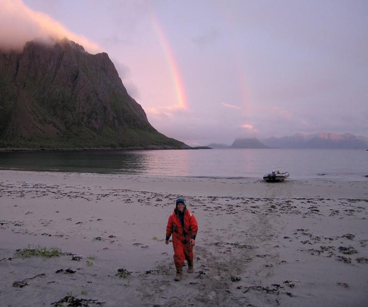 "GOING ON SHORE<br /> The sun was sinking to the horizon, colouring the world pink – as suddenly a rain burst over the mountains added a rainbow or two to the scenery, sort of to top the whole thing. The mountain ""Tinden"" protruded its summit into the clouds further out. Under such conditions the Sorsanden (the South Sand) is a paradise in this remarkable reign of islands. <br /> <br /> STRANDHUGG <br /> Solen dalte mot horisonten og farget verden rosa – da en byge over fjellene ga oss en regnbue eller to for å toppe det hele. Tinden stakk toppen inn i skyene i det fjerne. Under slike forhold er Sørsanden et paradis i dette forunderlige øyriket."