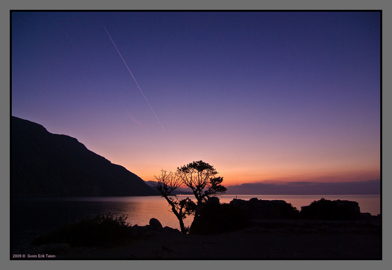 Another dawn - a single plane making a lonely stipe across the sky