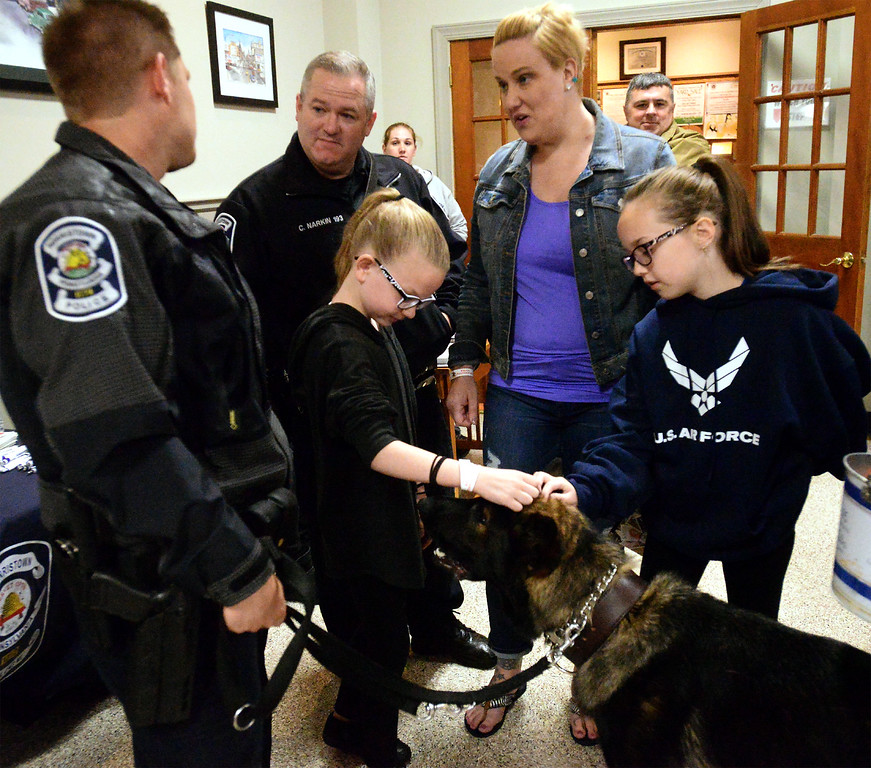. Meadow and Daisy Narkin pet Jerry, while K-9 officer Bryan Nawoschik chats with fellow K-9 Officer Christopher Narkin and his wife, Lisa, during a fundraiser at Maenner Chor Club May 13, 2017.