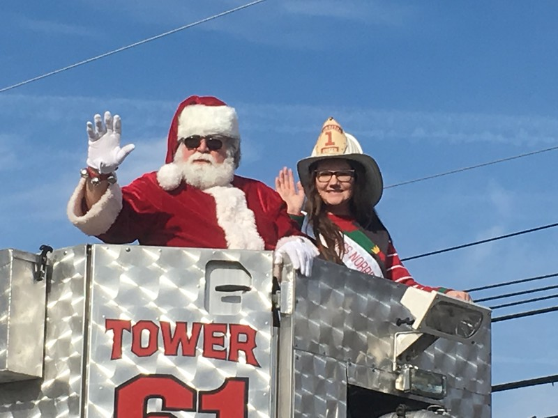 Santa Claus and Miss Norriton, Rose Matusheski, wave to the crowd from Tower 61 of the Norriton Fire Company during the East Norriton holiday parade Saturday, Dec. 2, 2017. (Joe Barron/Digital First Media)