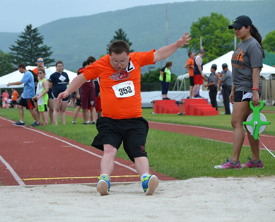 . Photo courtesy of Scott Otterbein Rob Decker competes in the long jump while Wicked Fast teammmates David Trott and Tom Gibson, far right in the background, receive medals for their efforts.